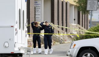 Police investigators Tuesday walk out of Oikos University in Oakland, Calif. The suspect in a deadly shooting at the college Monday is an expelled nursing student who said he felt disrespected by teasing about his poor English. (Associated Press)