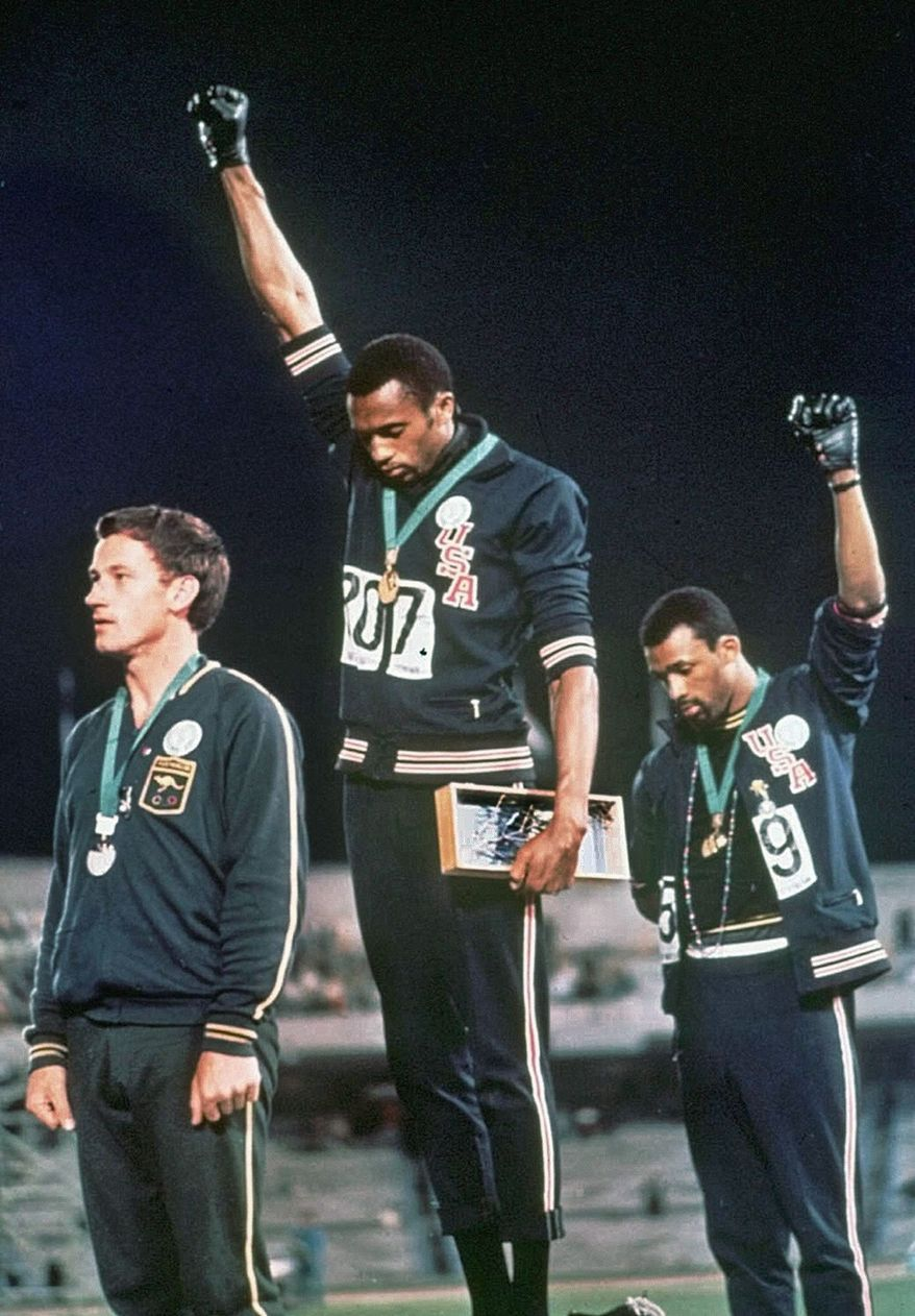 At the same 1968 Olympic games during which George Foreman waved an American flag to celebrate his victory, U.S. sprinters Tommie Smith (center) and John Carlos (right) stirred controversy when they gave a Black Power salute on the medals stand to protest racial injustice. (AP Photo)