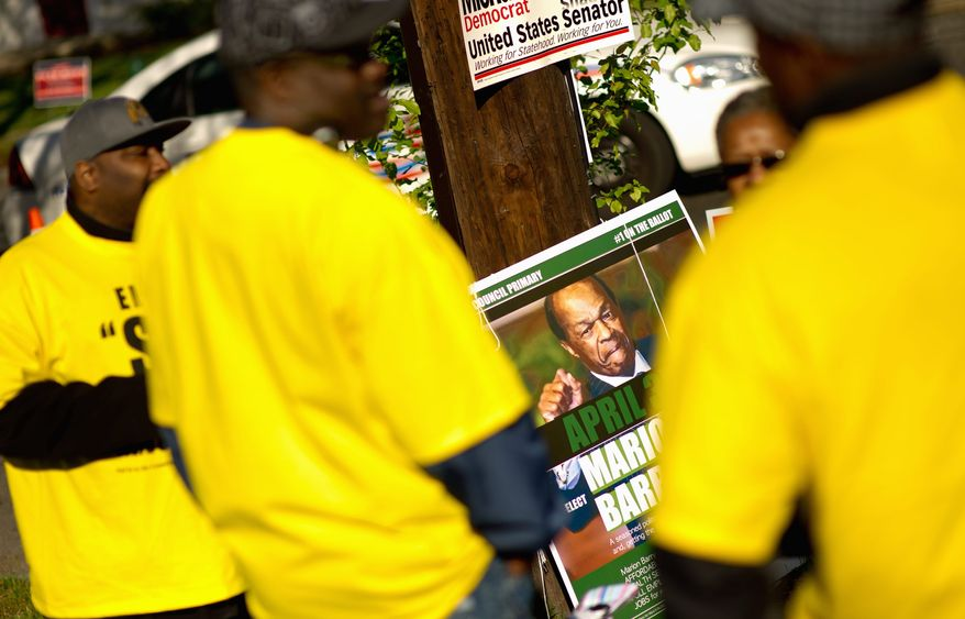 A poster promoting D.C. Council member Marion Barry, Ward 8 Democrat, is visible Tuesday behind volunteers for one of his challenger, Advisory Neighborhood Commissioner Sandra Seegers, outside New Image Baptist Church on Alabama Avenue in Southeast. (Andrew Harnik/The Washington Times)