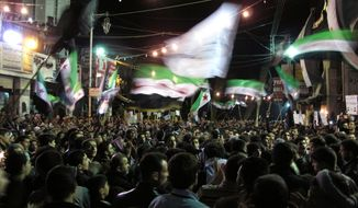 Syrians wave revolutionary flags and chant slogans April 2, 2012, at a night protest against President Bashar Assad in a neighborhood of Damascus, Syria. (Associated Press)