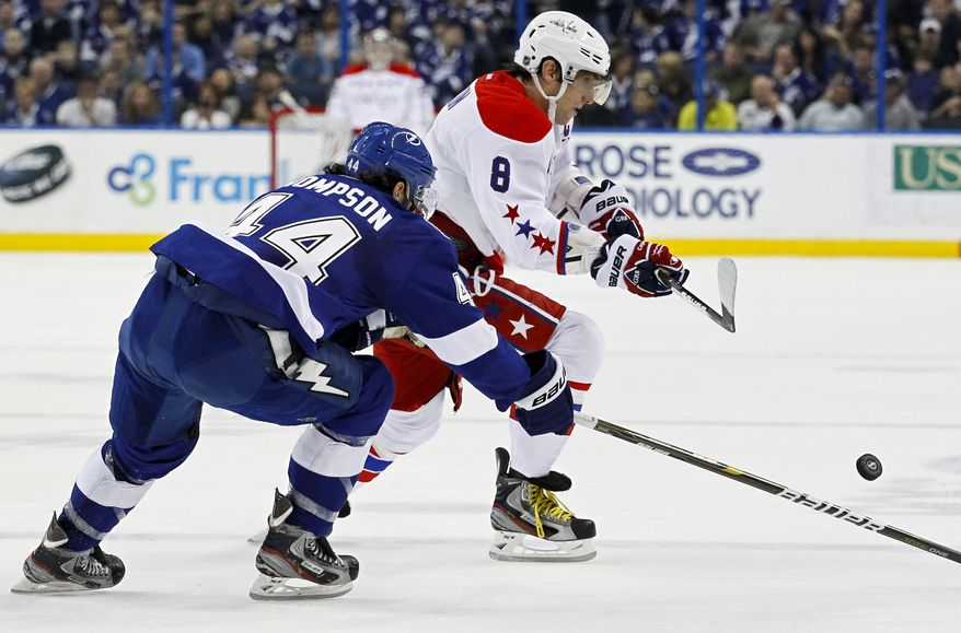 Tampa Bay Lightning's Nate Thompson, left, checks Washington Capitals' Alex Ovechkin, of Russia, during the first period of an NHL hockey game Monday, April 2, 2012, in Tampa, Fla. (AP Photo/Mike Carlson)
