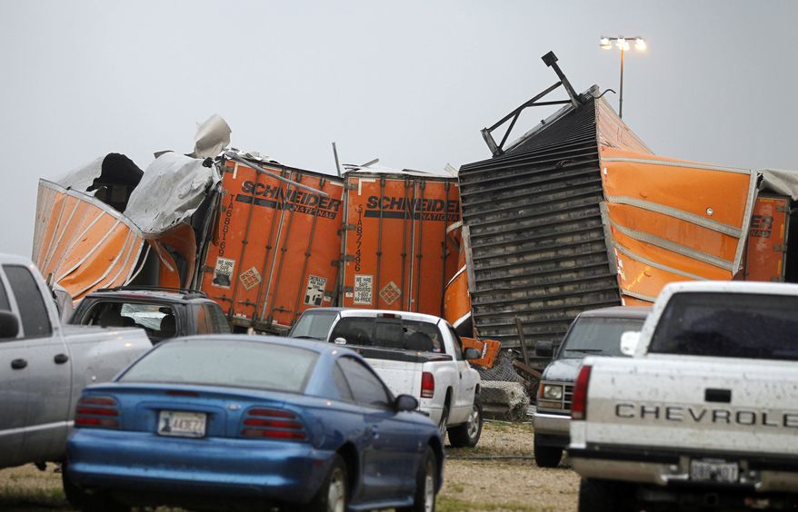 """Trailers lay smashed atop one another after a tornado reportedly tore through the southeastern portion of Dallas County, Texas, Tuesday, April 3, 2012, near Lancaster, Texas. The National Weather Service confirmed at least two separate """"large and extremely dangerous"""" tornadoes in the Dallas-Fort Worth area. (AP Photo/The Dallas Morning News, G.J. McCarthy)"""