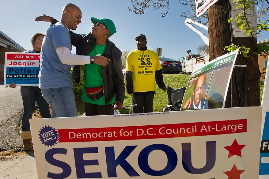 Posters for Ward 8 D.C. Council candidates surround former Ward 8 Democratic Party head Jacque Patterson (second from left), who is running for a council seat from the ward, as he hugs Kathy Arnold, a supporter of incumbent council member Marion Barry, also a Democrat, outside Precinct 116 at the New Image Baptist Church on Alabama Avenue Southeast in Washington on Tuesday, April 3, 2012. Also pictured is Jasmine Westbrook (left), a Howard University sophomore volunteering with Mr. Patterson, and Craig Leak (right), a volunteer with council candidate Sandra Seegers. (Andrew Harnik/The Washington Times)