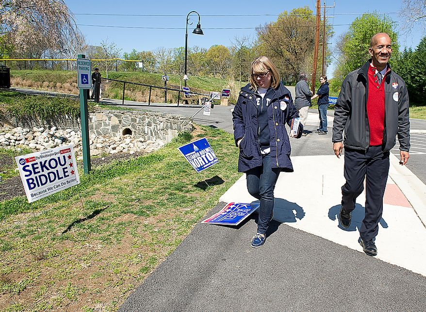 D.C. Council at-large candidate Sekou Biddle (right) leaves the Palisades Recreation Center on Tuesday, April 3, 2012. Mr. Biddle visited polling places in every ward for the D.C. primary election on Tuesday, April 3, 2012. (Barbara L. Salisbury/The Washington Times)