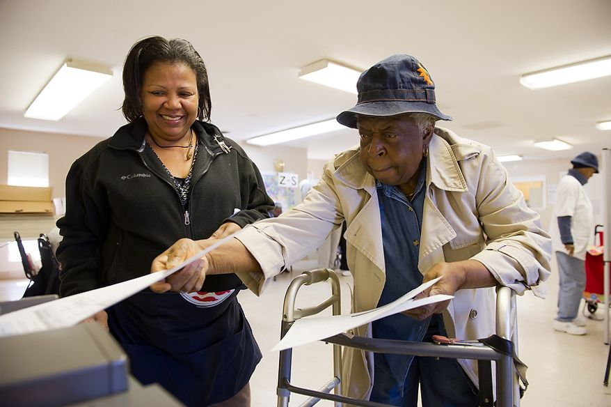 Assistant poll captain Glinder Barnes (left) helps Mattie B. Butts (right) cast her vote at Precinct 116 inside the New Image Baptist Church on Alabama Avenue Southeast in Washington on Tuesday, April 3, 2012. (Andrew Harnik/The Washington Times)