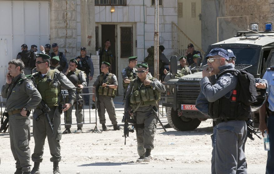 Israeli security forces surround a house illegally occupied by Jewish settlers in the West Bank city of Hebron, Wednesday, April 4, 2012. Israeli security forces began evicting dozens of settlers Wednesday from a building they illegally took over and lived in without the required military approval in Hebron, police said. (AP Photo/Sebastian Scheiner)
