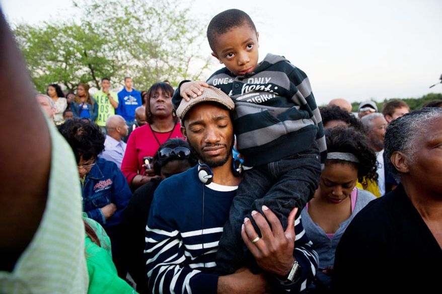 Steven Harris of Atlanta, Ga. holds his son Joyce, 6, for a moment of silence during a candle light vigil at the Martin Luther King, Jr. Memorial on the 44th Anniversary of King's assassination. (Andrew Harnik/The Washington Times)