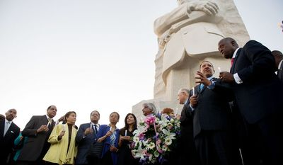 Dignitaries including Delegate Eleanor Holmes Norton (fifth from right), D.C. Democrat; Christine Chavez (sixth from right,), the granddaughter of Cesar Chavez; Arun Gandhi (fifth from right), the grandson of Mahatma Gandhi; Harry Johnson (right), president and CEO of the Martin Luther King Jr. Memorial Project; and Marc Morial (second from right), president of the National Urban League, lead a candlelight vigil at the Martin Luther King Jr. Memorial. (Andrew Harnik/The Washington Times)