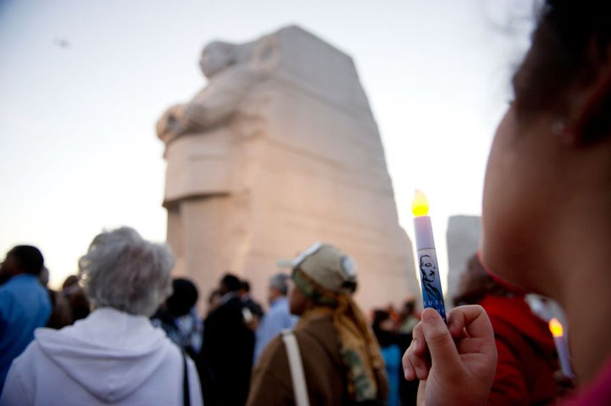Cristina Rivera of St. Louis, Mo., right, holds an L.E.D. candle as dignitaries lead a candle light vigil at the Martin Luther King, Jr. Memorial. (Andrew Harnik/The Washington Times)
