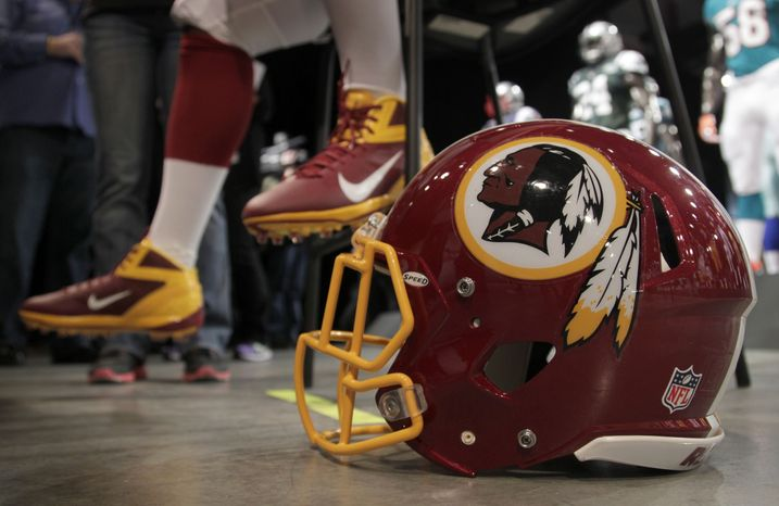 A Washington Redskins player is interviewed April 3, 2012, while his helmet sits on the floor during a presentation in New York. (Associated Press)