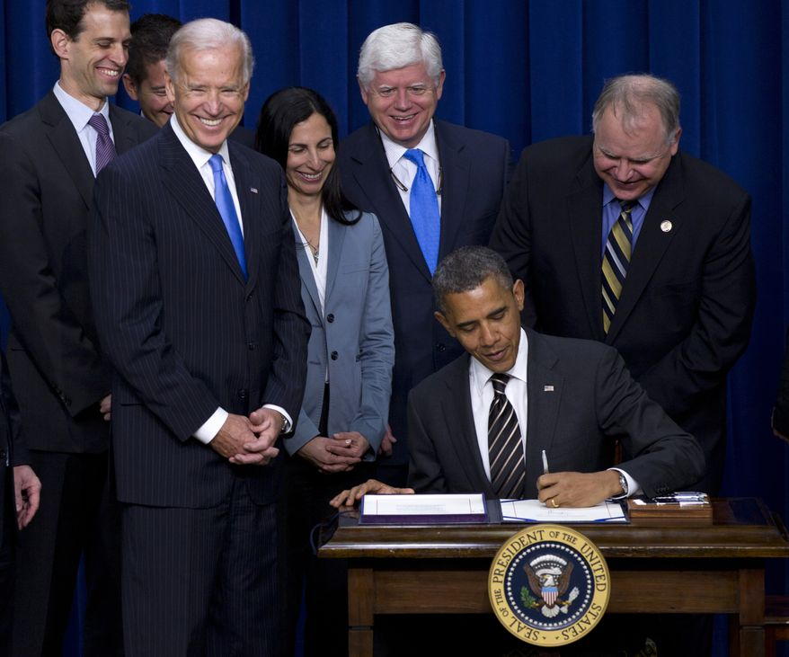 President Barack Obama signs the Stop Trading on Congressional Knowledge (STOCK) Act, Wednesday, April 4, 2012, in the Eisenhower Executive Office Building on the White House complex in Washington. Vice President Joe Biden and others watch. (AP Photo/Carolyn Kaster)