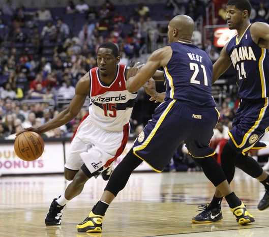 Washington Wizards shooting guard Jordan Crawford (15) drives past Indiana Pacers forward David West (21) and Indiana Pacers shooting guard Paul George (24) during the first half of an NBA basketball game on Wednesday, April 4, 2012, in Washington. (AP Photo/Evan Vucci)