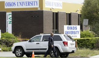 An Oakland police officer walks outside of Oikos University in Oakland, Calif., on Tuesday, April 3, 2012. (AP Photo/Jeff Chiu)
