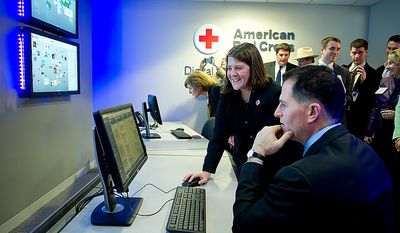 Wendy Harman, left, director of social engagement for the American Red Cross, walks Michael Dell, founder and CEO of Dell Inc., through the operations and capabilities of the newly unveiled American Red Cross Digital Operations Center powered by Dell on Wednesday, March 7, 2012, at the American Red Cross headquarters in Washington, D.C. The Digital Operations Center is devoted to disaster relief and uses social media to help empower communities during and after local disasters. (Barbara L. Salisbury/The Washington Times)