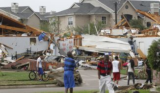 Neighbors view what remains of a home in Arlington, Texas, on Tuesday, April 3, 2012, after tornadoes tore through the Dallas-Fort Worth area. (AP Photo/Fort Worth Star-Telegram, Ron Jenkins)