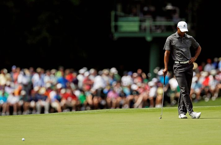 Tiger Woods reflects on his shot after missing a birdie putt on the 15th hole. Woods shot a par 72 and is five back of leader Lee Westwood. (Associated Press)