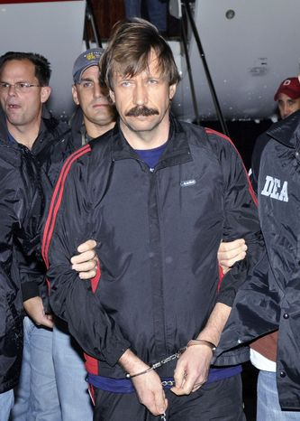 Viktor Bout in 2010 is led off a flight from Bangkok to New York during his extradition to face trial on charges of transporting weapons. (Associated Press)