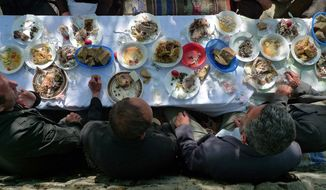 Orthodox Christian and Muslim shepherds share an Easter meal in front of the house of shephard Anastas Karaj in the village of Selta in central Albania. Easter bread, fresh olives, puff pastry and goat meat are all part of the traditional Easter meal. (Eckehard Pistrick/Special to The Washington Times)