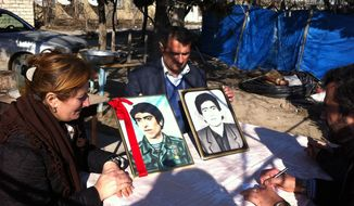 Figura Rustamova and her husband, Avaz Hasanov, show photos of Rustamova's brother, Furzoli (left), who was killed during the Khojaly Massacre, and a neighbor who was also a victim of the tragedy. (Eric J. Lyman/Special to The Washington Times)