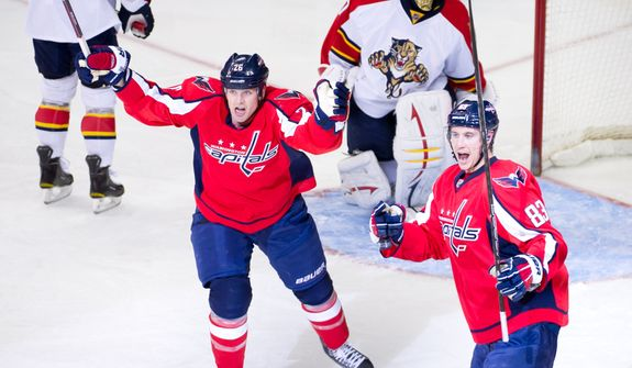 Washington Capitals left wing Matt Hendricks (26), second from left, celebrates as Washington Capitals center Jay Beagle (83), right, scores on Florida Panthers goalie Jose Theodore (60) to bring the Washington Capitals up 1-0 against the Florida Panthers in the first period during National Hockey League hockey at the Verizon Center, Washington, D.C., Thursday, April 5, 2012. (Andrew Harnik/The Washington Times)