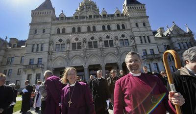 Bishop Suffragan Laura J. Ahrens (left) and Bishop Ian T. Douglas (right) of the Episcopal Diocese of Connecticut demonstrate against the death penalty along with other religious leaders at the state Capitol in Hartford, Conn., on Tuesday, April 3, 2012. (AP Photo/Jessica Hill)