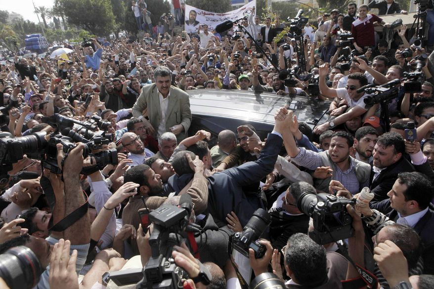 Hundreds of Egyptian supporters of Muslim Brotherhood presidential hopeful Khairat el-Shater surround his car outside the Higher Presidential Elections Commission in Cairo on April 5, 2012. (Associated Press)
