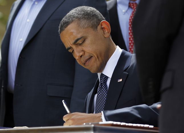 President Obama signs the Jumpstart Our Business Startups (JOBS) Act on April 5, 2012, in the Rose Garden of the White House. (Associated Press)