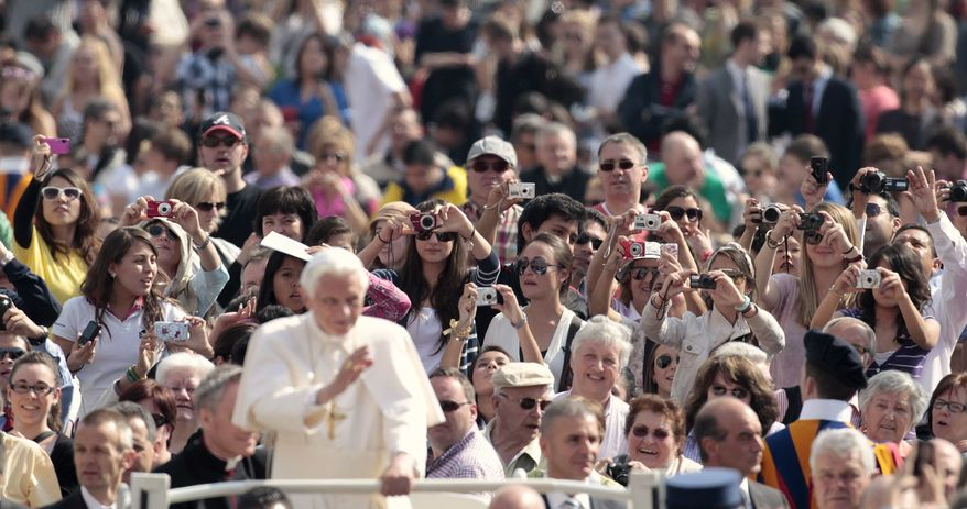 Pope Benedict XVI (foreground) is photographed by the faithful as he tours St. Peter's Square during his weekly general audience at the Vatican on Wednesday, April 4, 2012. (AP Photo/Gregorio Borgia)