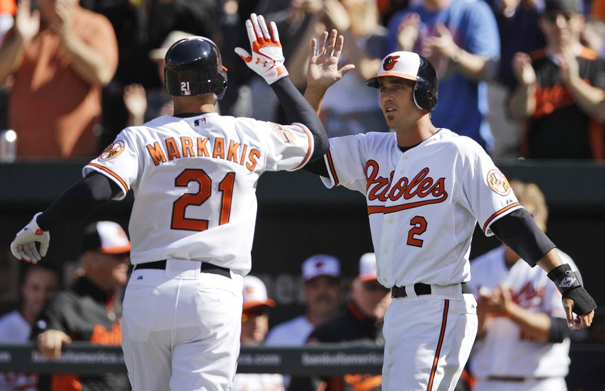 Baltimore Orioles' J.J. Hardy, right, greets Nick Markakis at home plate after he hit a home run against the the Minnesota Twins in Baltimore on Friday, April 6, 2012. (AP Photo/Patrick Semansky)