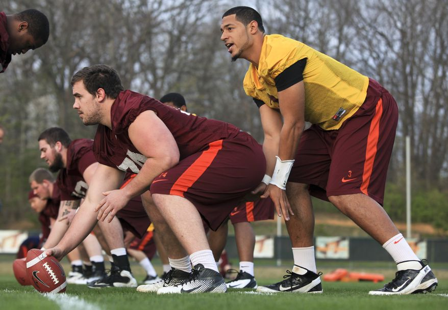 Virginia Tech quarterback Logan Thomas, right, takes a snap from center Andrew Miller, front left, during the opening day of spring NCAA college football drills on campus in Blacksburg, Va., on Wednesday, March 28, 2012. (AP Photo/The Roanoke Times, Matt Gentry)