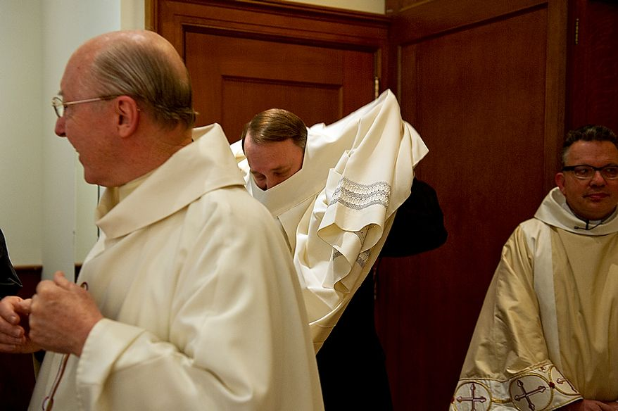 Father Mark Knestout (center), director of the office of worship for the Archdiocese of Washington, gets into his vestments for the Mass of the Lord's Supper at the Cathedral of St. Matthew the Apostle in Washington, D.C., on April 5, 2012, which was Holy Thursday. (Barbara L. Salisbury/The Washington Times)