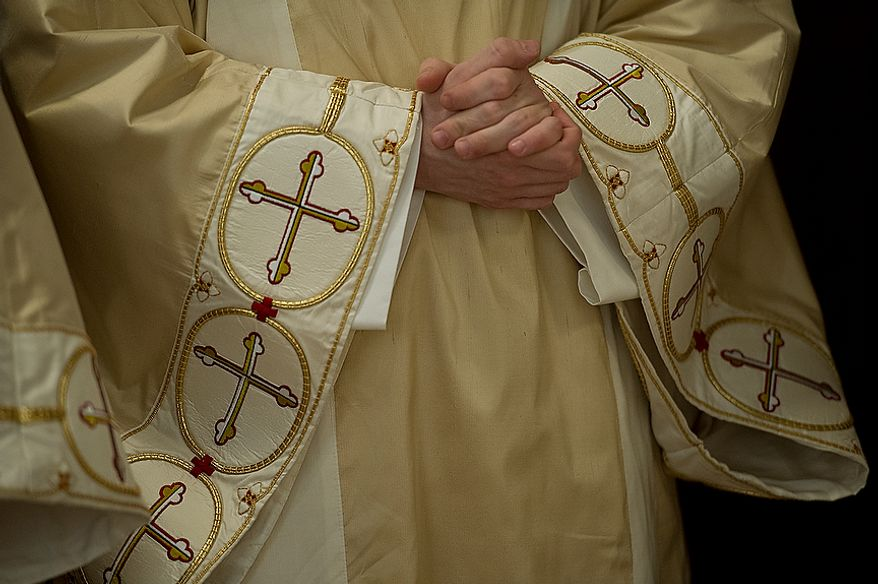 A priest wearing a chasuble, a ceremonial vestment, holds his hands in prayer as he awaits the beginning of the Mass of the Lord's Supper at the Cathedral of St. Matthew the Apostle in Washington, D.C., on April 5, 2012, which was Holy Thursday. (Barbara L. Salisbury/The Washington Times)