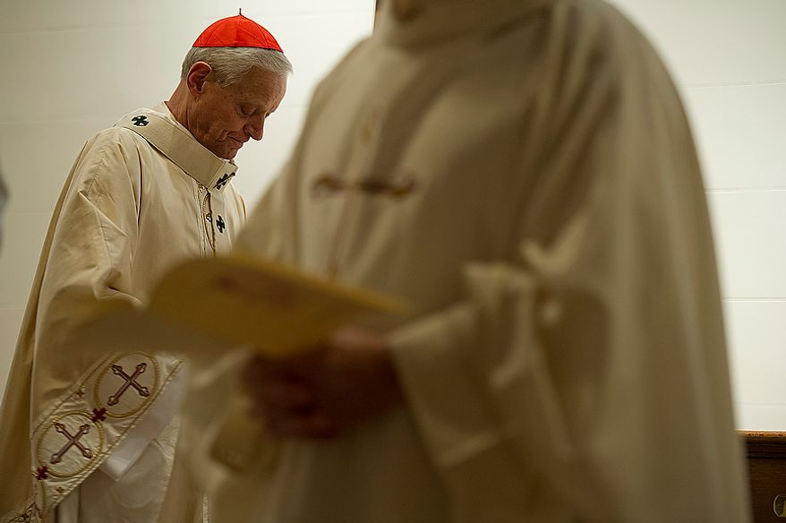 Cardinal Donald Wuerl (left), archbishop of Washington, waits for the beginning processional of the Mass of the Lord's Supper at the Cathedral of St. Matthew the Apostle in Washington, D.C., on April 5, 2012, which was Holy Thursday. (Barbara L. Salisbury/The Washington Times)