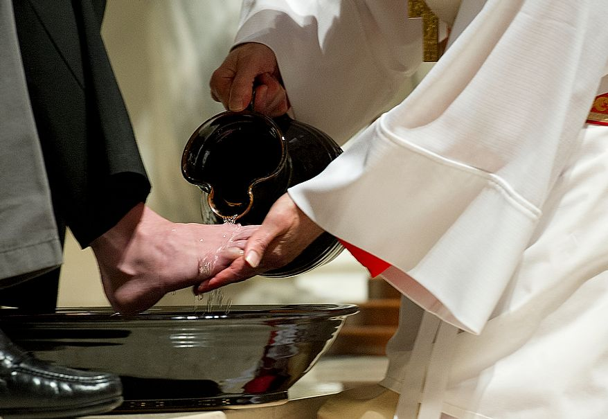 """Cardinal Donald Wuerl, archbishop of Washington, washes feet during the Mass of the Lord's Supper at the Cathedral of St. Matthew the Apostle in Washington, D.C. on Holy Thursday, April 5, 2012. The washing of the feet is a religious rite that represents Jesus washing his disciples' feet, saying """"A servant is no greater than his master."""" (Barbara L. Salisbury/The Washington Times)"""