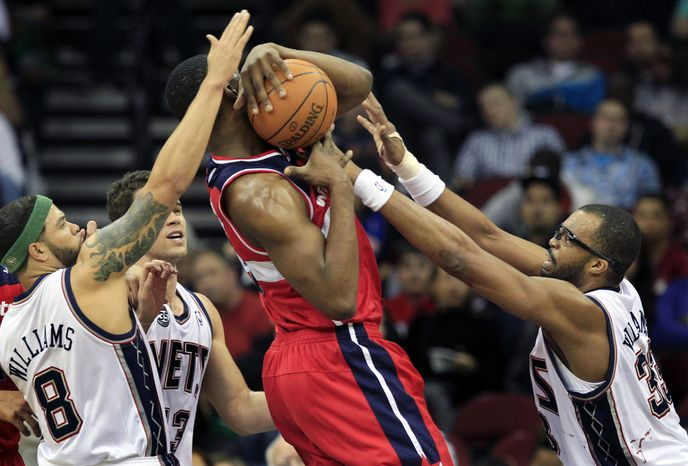 New Jersey Nets' Shelden Williams, right, Deron Williams, left, and Kris Humphries, second from left, block a shot by Washington Wizards' Kevin Seraphin during the first half in Newark, N.J., on Friday, April 6, 2012. The Nets won 110-98. (AP Photo/Mel Evans)