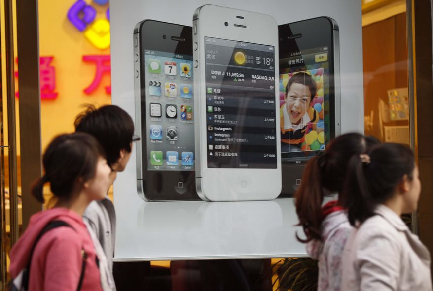 Chinese walk in front of an iPhone poster at a phone shop in Beijing Saturday, April 7, 2012. Authorities indicted five people in central China for involvement in illegal organ trading after a teenager sold one of his kidneys to buy an iPhone and an iPad. (AP Photo/ Vincent Thian)