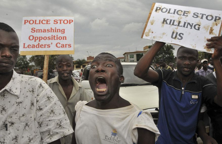 """Ugandan opposition members, vowing to resist their criminalisation by the government, demonstrate in Kampala, Uganda, Thursday, April 5, 2012. The Ugandan government on Wednesday outlawed the group """"Activists for Change"""" that since last year has led popular protests against official corruption and the high cost of living, saying it had become a force for instability. (AP Photo/Stephen Wandera)"""