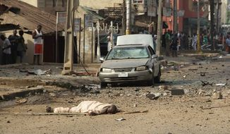 A body lands in the middle of the street at the site of a car-bomb explosion on a road in Kaduna on Sunday. (Associated Press)
