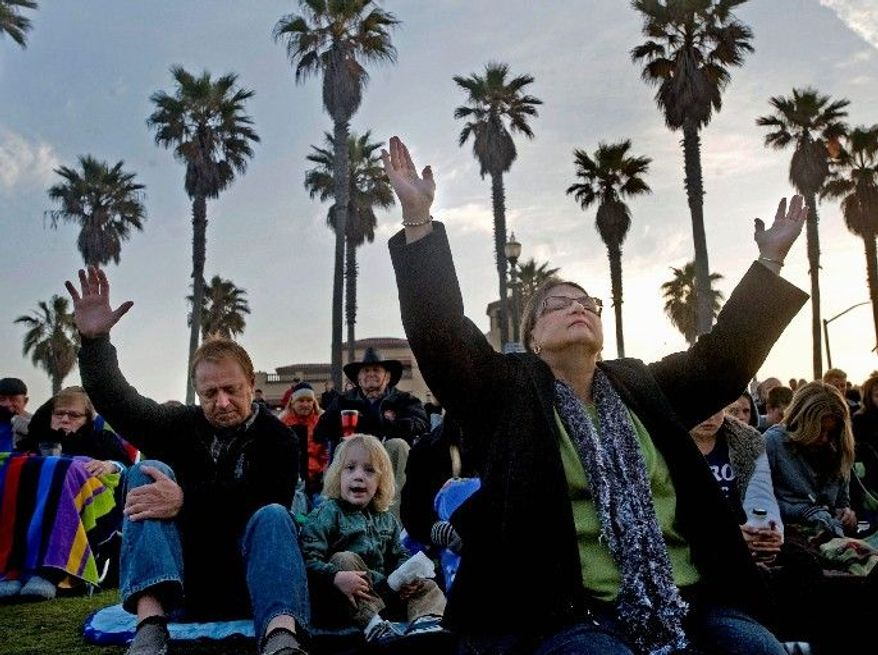 Art Menendez (left) and Javern Carothers, of Costa Mesa, Calif., raise their hands in prayer during the Surf City Alive Easter sunrise service in Huntington Beach, Calif. (Orange County Register via Associated Press)