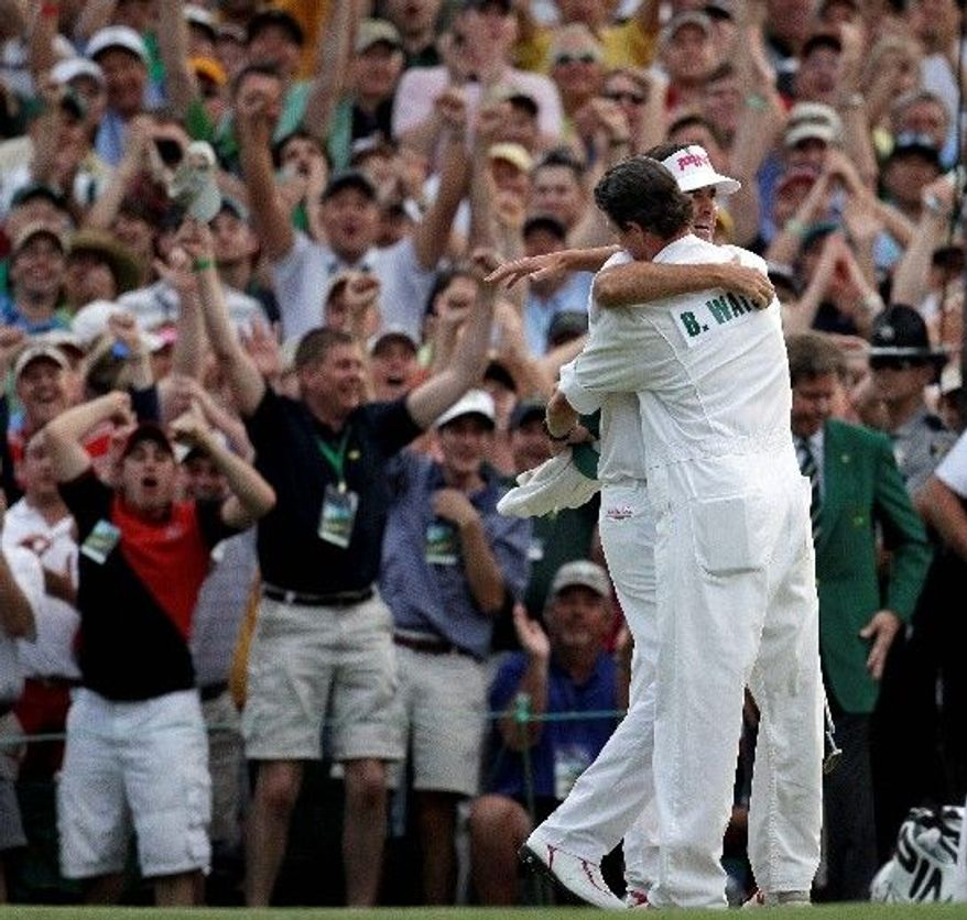 Bubba Watson embraces caddie Ted Scott after winning the Masters in a sudden death playoff over Louis Oosthuizen on the 10th hole (above). Both players finished 72 holes at 10-under 278.(Associated Press)