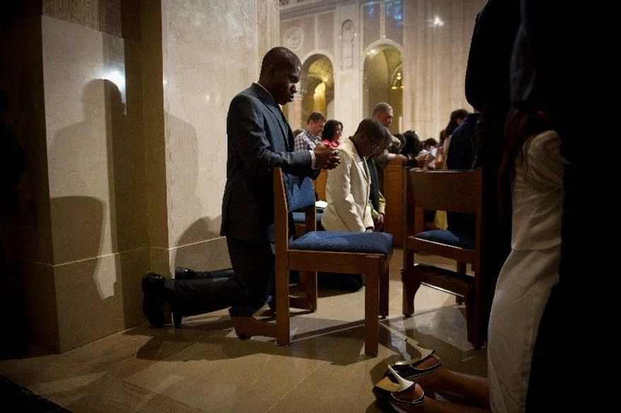 Hilary Unaegbu of Bowie kneels in prayer, during the Easter Sunday Mass at the Basilica of the National Shrine of the Immaculate Conception in Washington. (Rod Lamkey Jr./The Washington Times)