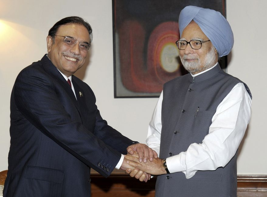Pakistani President Asif Ali Zardari (left) shakes hands with Indian Prime Minister Manmohan Singh before their meeting at the latter's residence in New Delhi on Sunday, April 8, 2012. (AP Photo/Indian Press Information Bureau)