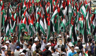 Pro-Syrian-government demonstrators hold Baath party flags and a picture of President Bashar Assad at a rally at Sabe Bahrat Square in Damascus, Syria, on Saturday, April 7, 2012, to commemorate the 65th anniversary of the founding of the ruling Baath Arab Socialist Party. (AP Photo/Bassem Tellawi)