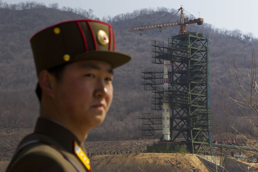 ** FILE ** A North Korean soldier stands in front of the country's Unha-3 rocket, which was launched unsuccessfully on Friday, April 13, 2012. (AP Photo/David Guttenfelder)