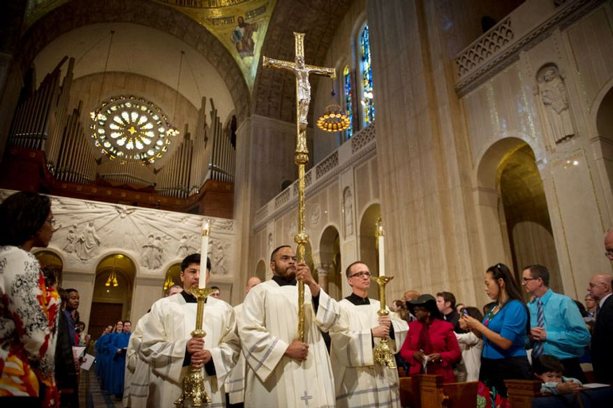 The procession makes it way up the aisle for the Easter Sunday Solemn Mass at the Basilica of the National Shrine of the Immaculate Conception. (Rod Lamkey Jr/The Washington Times)