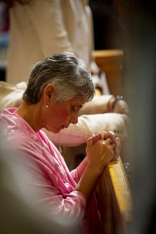 A woman kneels in prayer at the Basilica of the National Shrine of the Immaculate Conception. (Rod Lamkey Jr/The Washington Times)