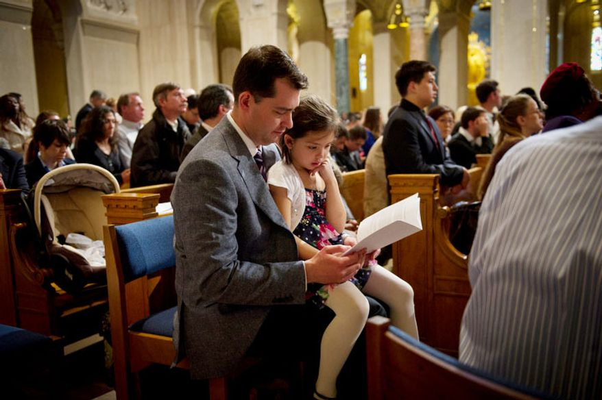 Ray Krncevic, of Cleveland, Ohio, sits with his six year-old daughter Christina in the pews during the Easter Sunday Solemn Mass. (Rod Lamkey Jr/The Washington Times)