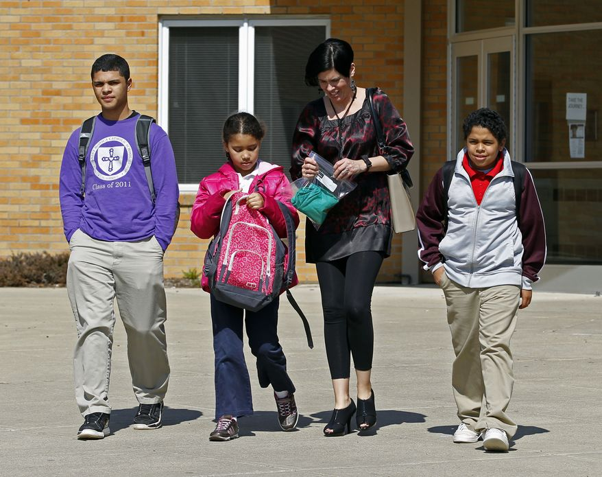 ** FILE ** In this March 16, 2011 photo, Heather Coffy, right center, leaves the St. Monica School in Indianapolis with her children, left to right, Delano Coffy, 15, Alanna Marshall, 8, and Darius Coffy, 11. Students like Delano are at the heart of brewing political fights and court battles over whether public dollars should go to vouchers to help make private schools more affordable. (AP Photo/Michael Conroy, File)