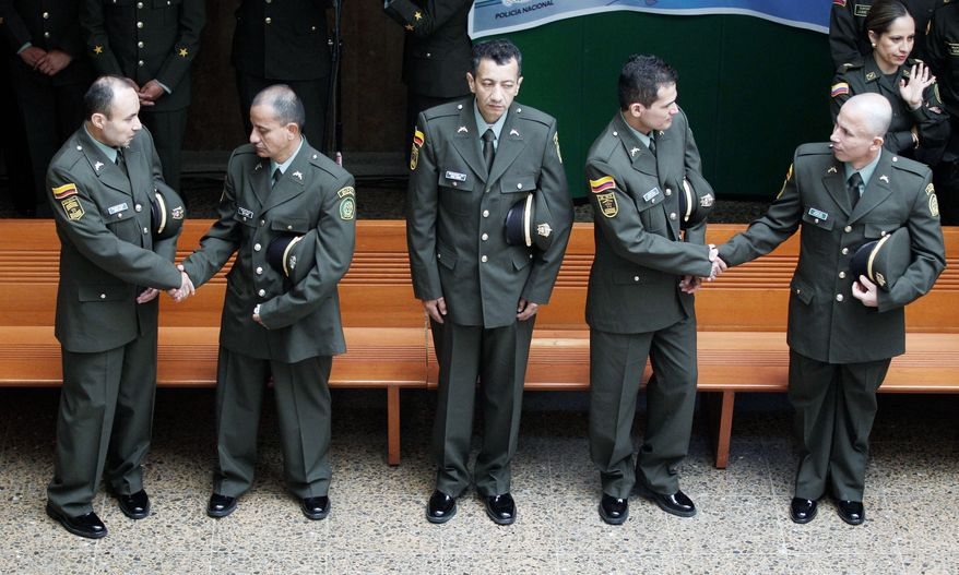 Former hostages Cesar Augusto Lasso (from left), Jose Forero, Jorge Romero, Carlos Duarte and Wilson Rojas greet each other at police headquarters in Bogota, Colombia, on April 4. The men had spent between 12 and 14 years in jungle prisons. They were captured when the Revolutionary Armed Forces of Colombia was at the height of its military strength. (Associated Press)
