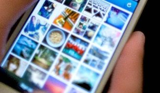 Facebook is spending $1 billion to buy Instagram, a photo-sharing app in use on an iPhone. It is paying cash and stock for the company and hiring its dozen or so employees. (Associated Press)